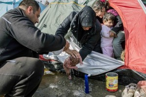 Refugees washing a newborn baby with a bottle of water. Photo credit - Getty Images